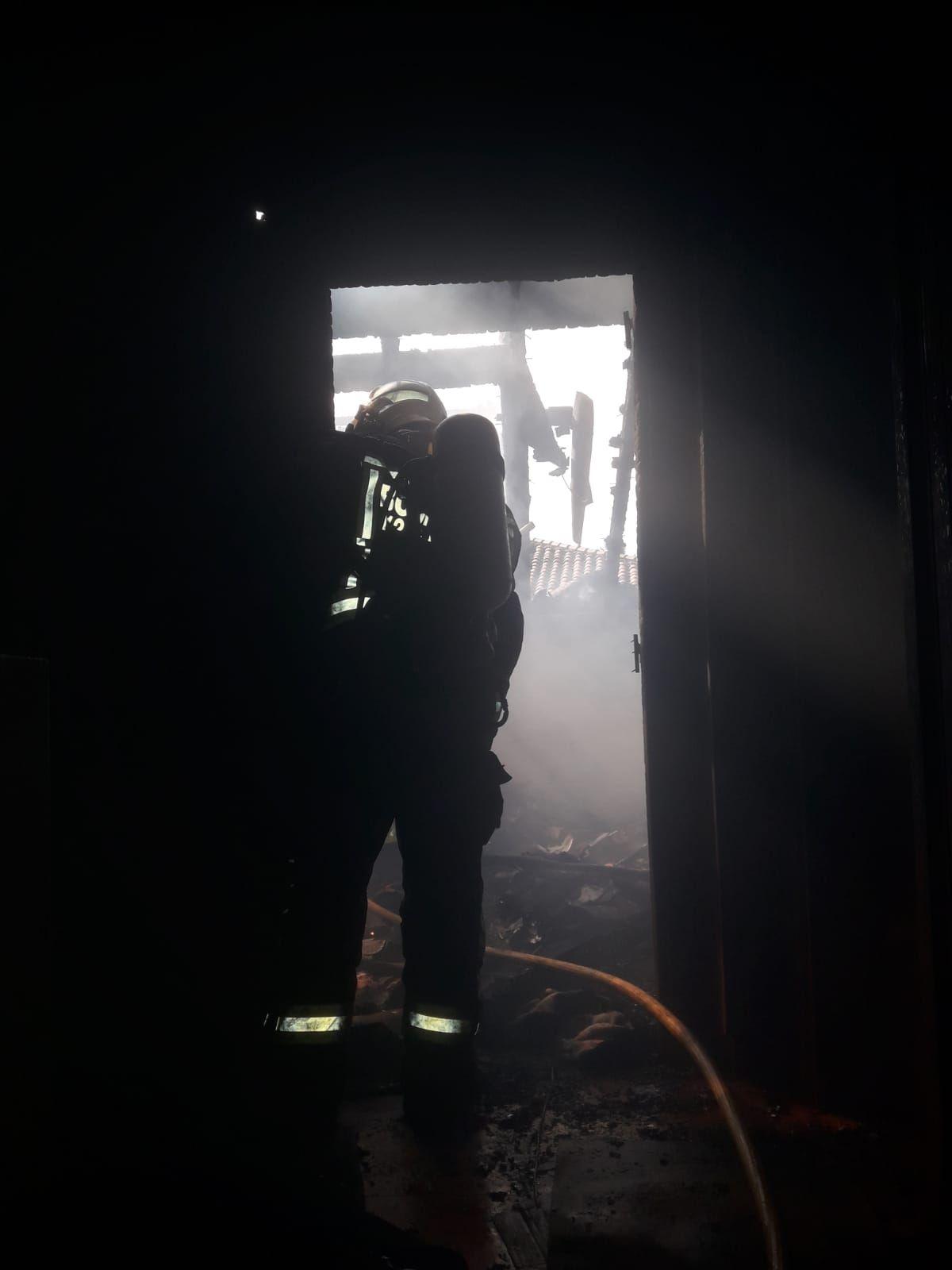 bombero en el interior de la vivienda quemada