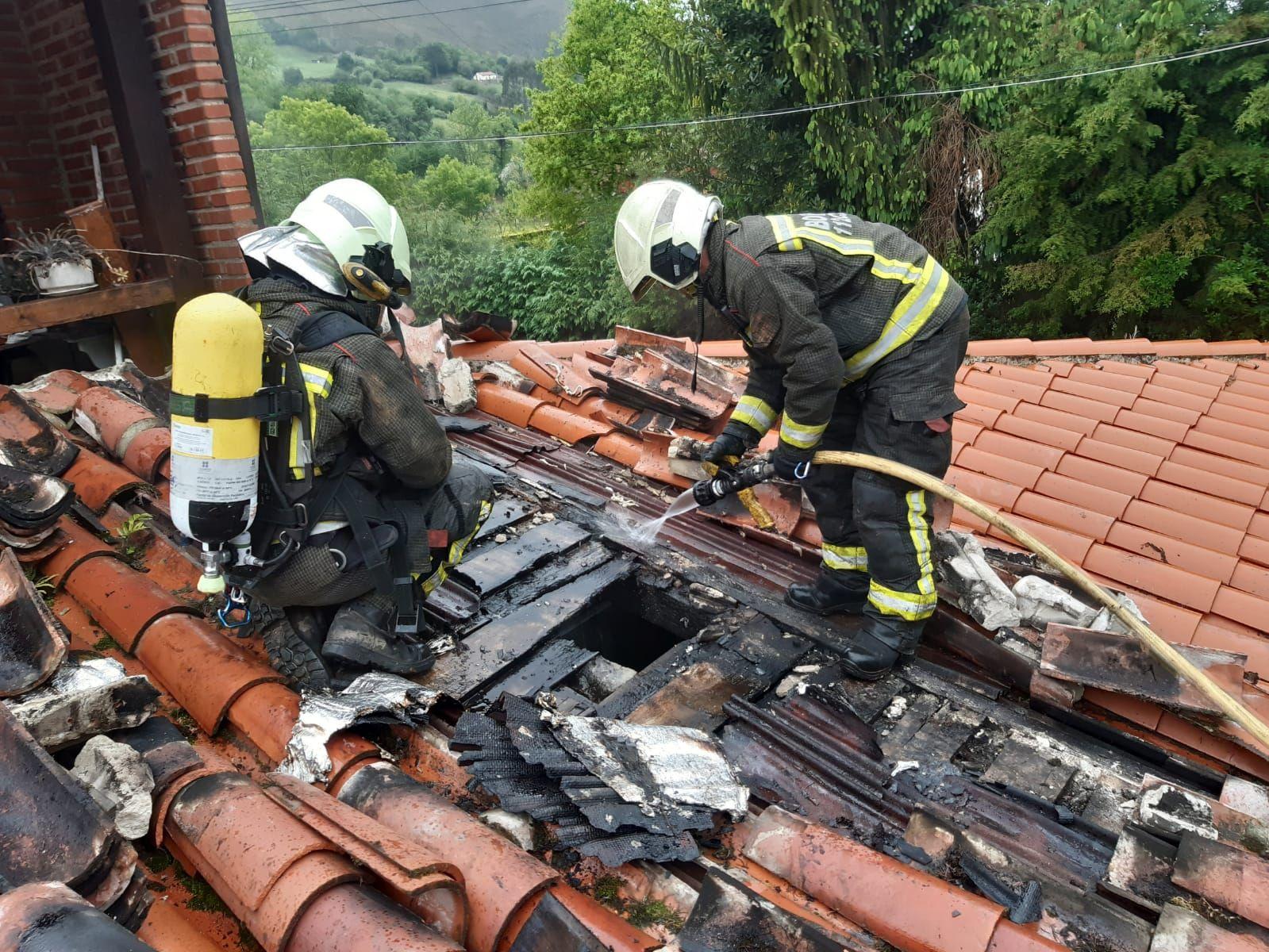 bomberos en el tejado refrigerando la zona quemada