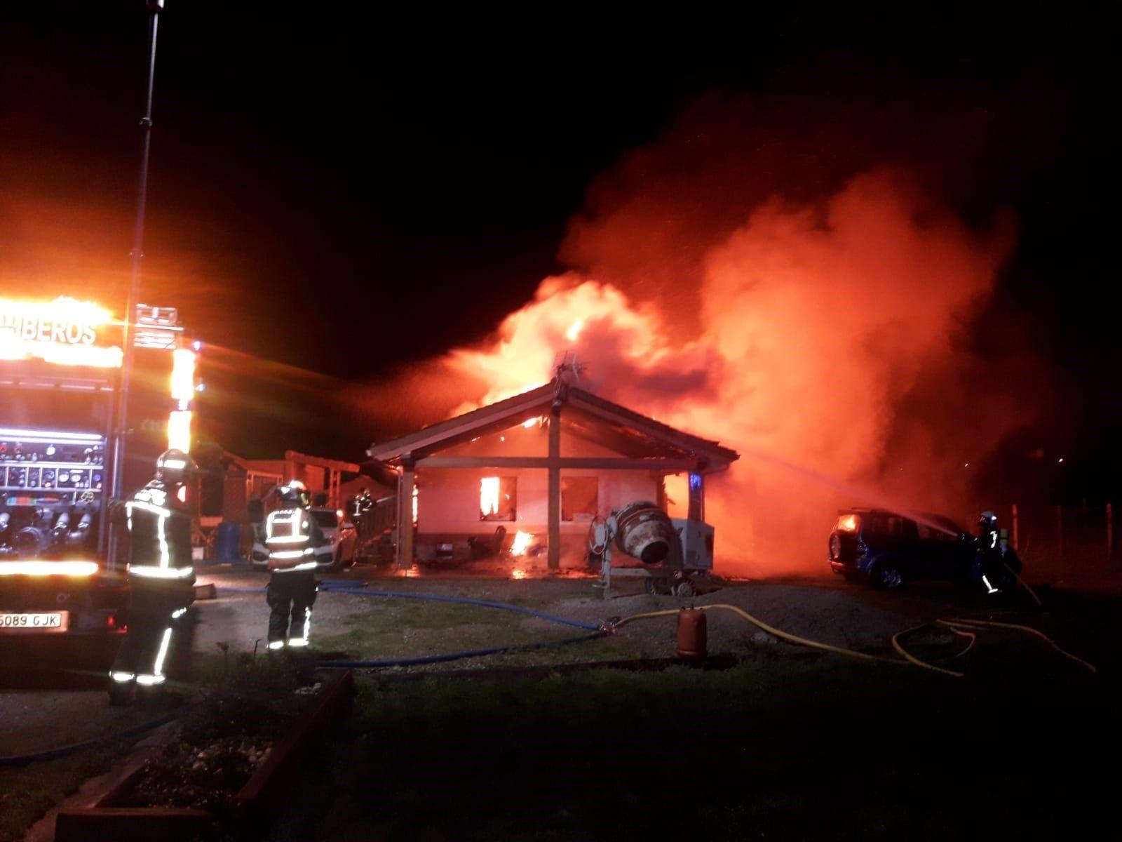 Bomberos ante la casa en llamas