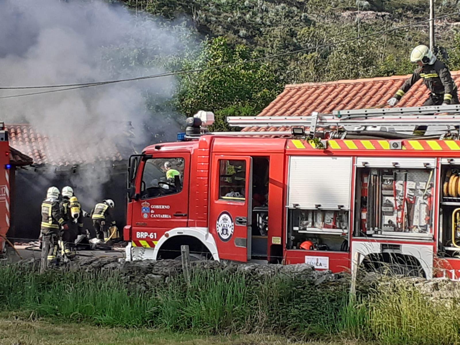 escena del incendio con bomberos en el camión y el garaje