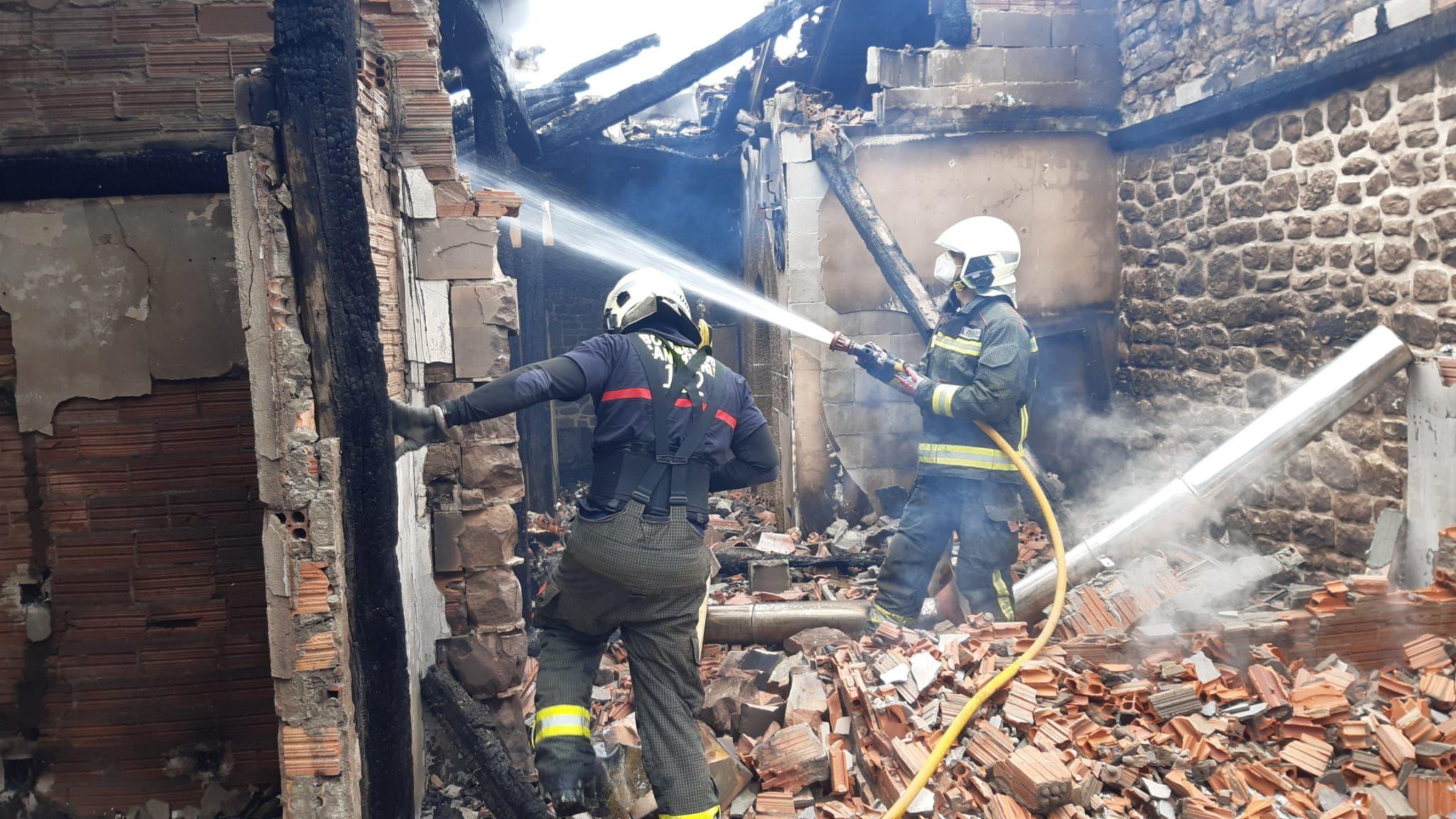 dos bomberos refrescando el escombro generado